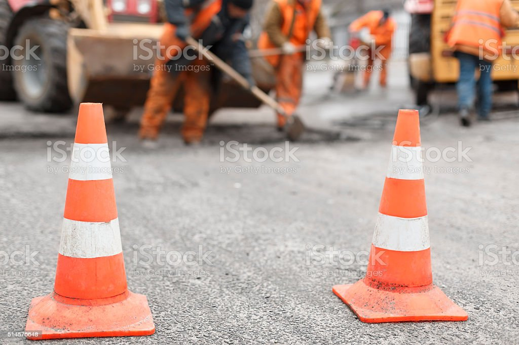 road workers repair the road,  cones in  foreground stock photo