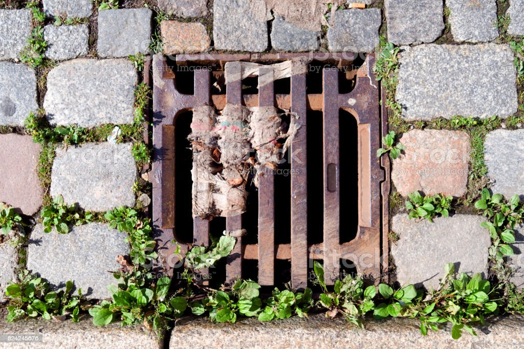 Roads: Polluted gully cover stock photo