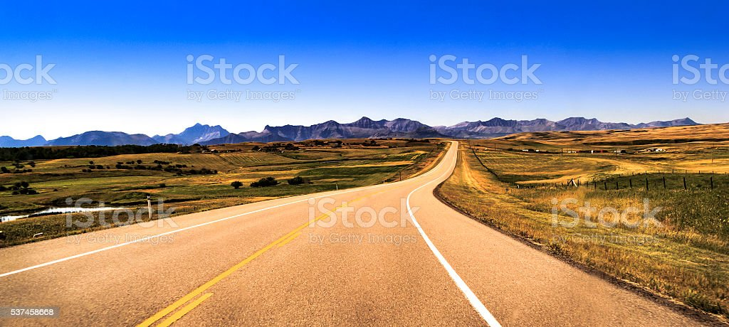 Roadtrip road stretching towards Waterton and Rocky Mountains stock photo