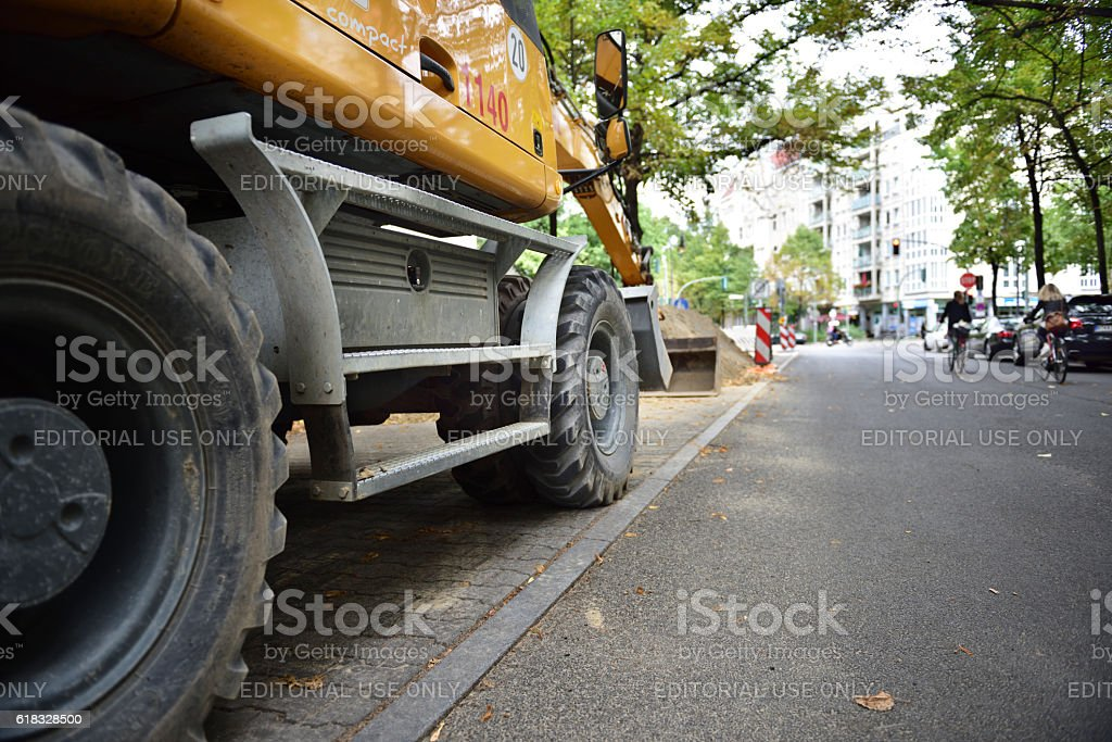 Roadwork ongoing. Digger close up. Bikes in traffic in background. stock photo