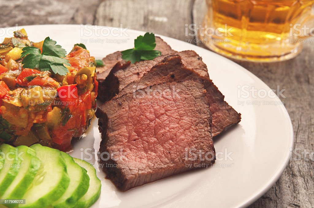 Roast beef on white plate with vegetable ragout stock photo