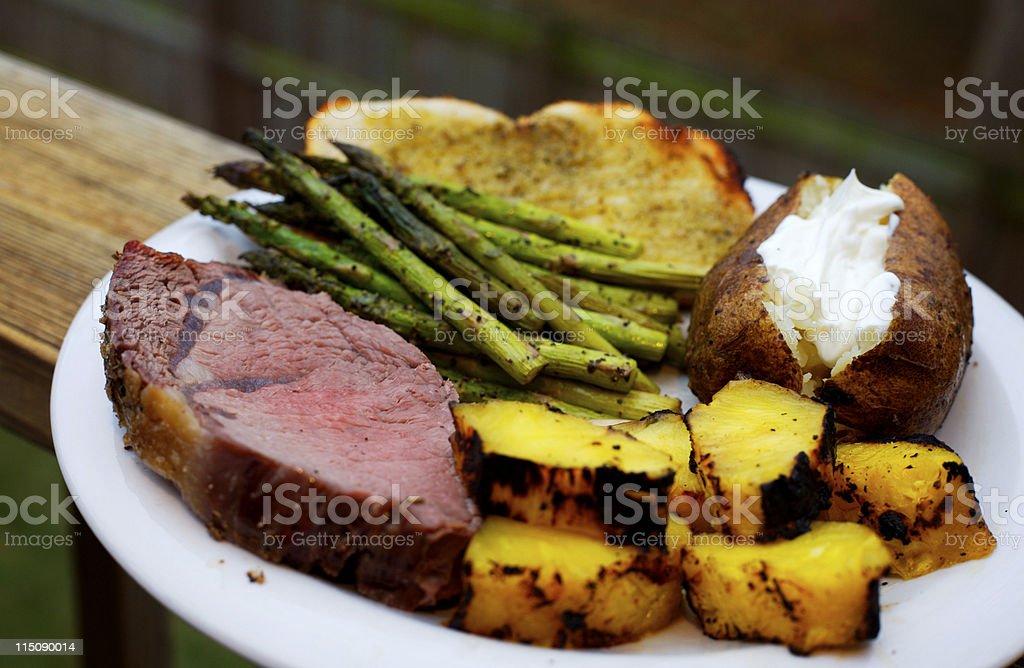 roast beef prime rib asparagus baked potato platter royalty-free stock photo
