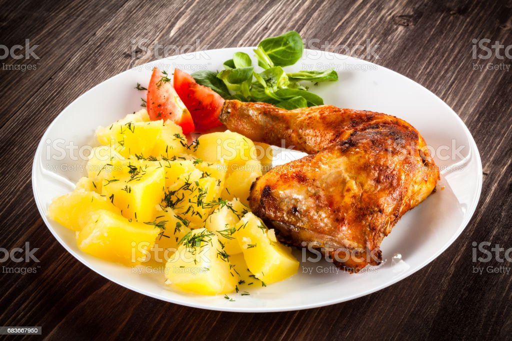 Roast chicken leg and vegetables stock photo
