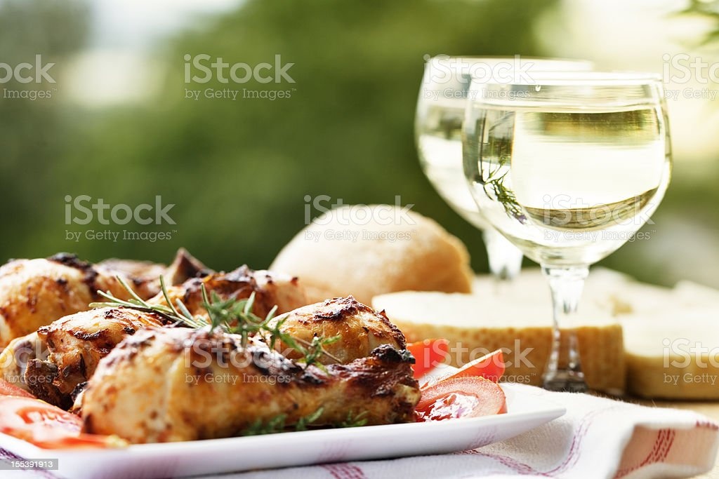 roast chicken legs and white wine at picnic royalty-free stock photo