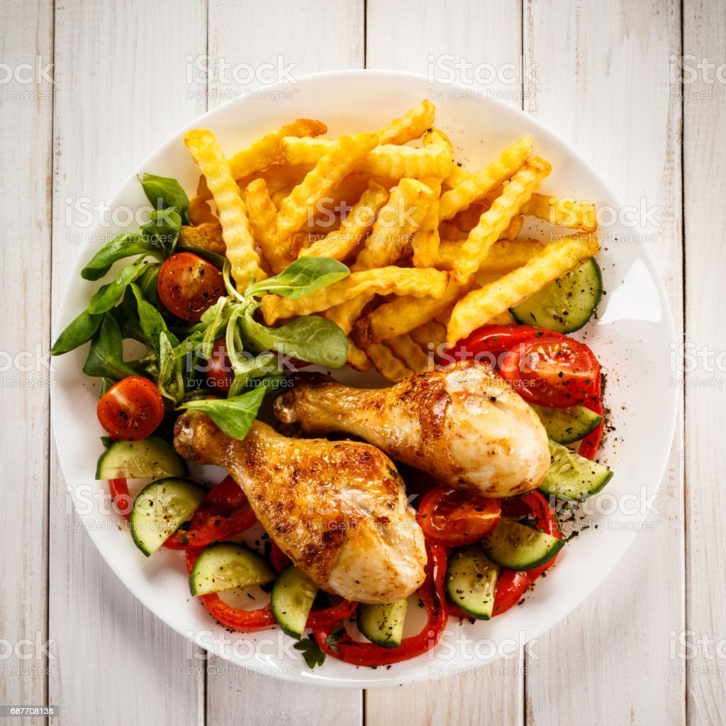 Roast chicken legs with chips and vegetables stock photo