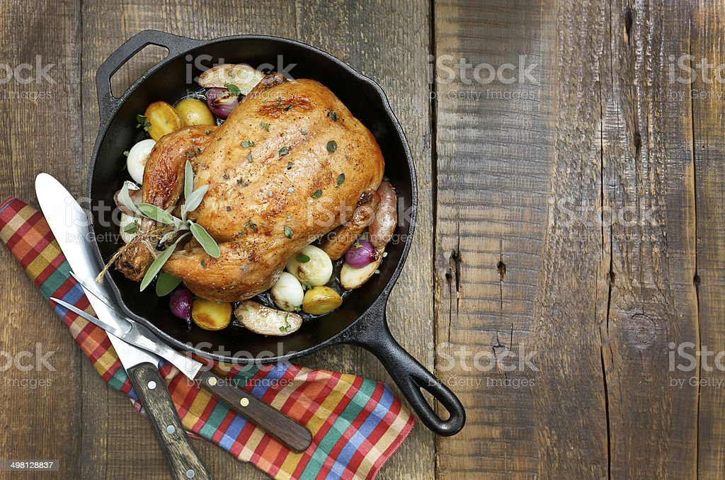 Roast Chicken with Potatoes and Onions in Cast Iron Pan. stock photo