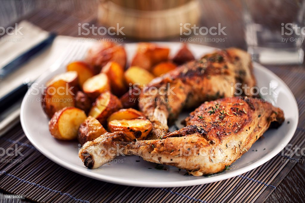 Roast chicken with potatoes on a plate stock photo
