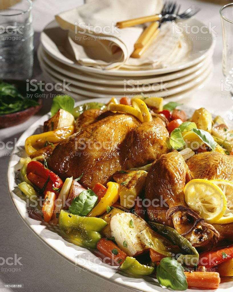 Roast chicken with vegetables on serving tray. stock photo