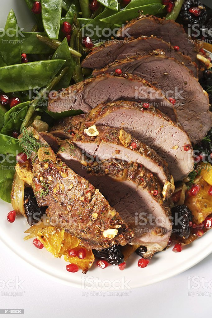 A roast cooked Christmas lamb on a white plays royalty-free stock photo