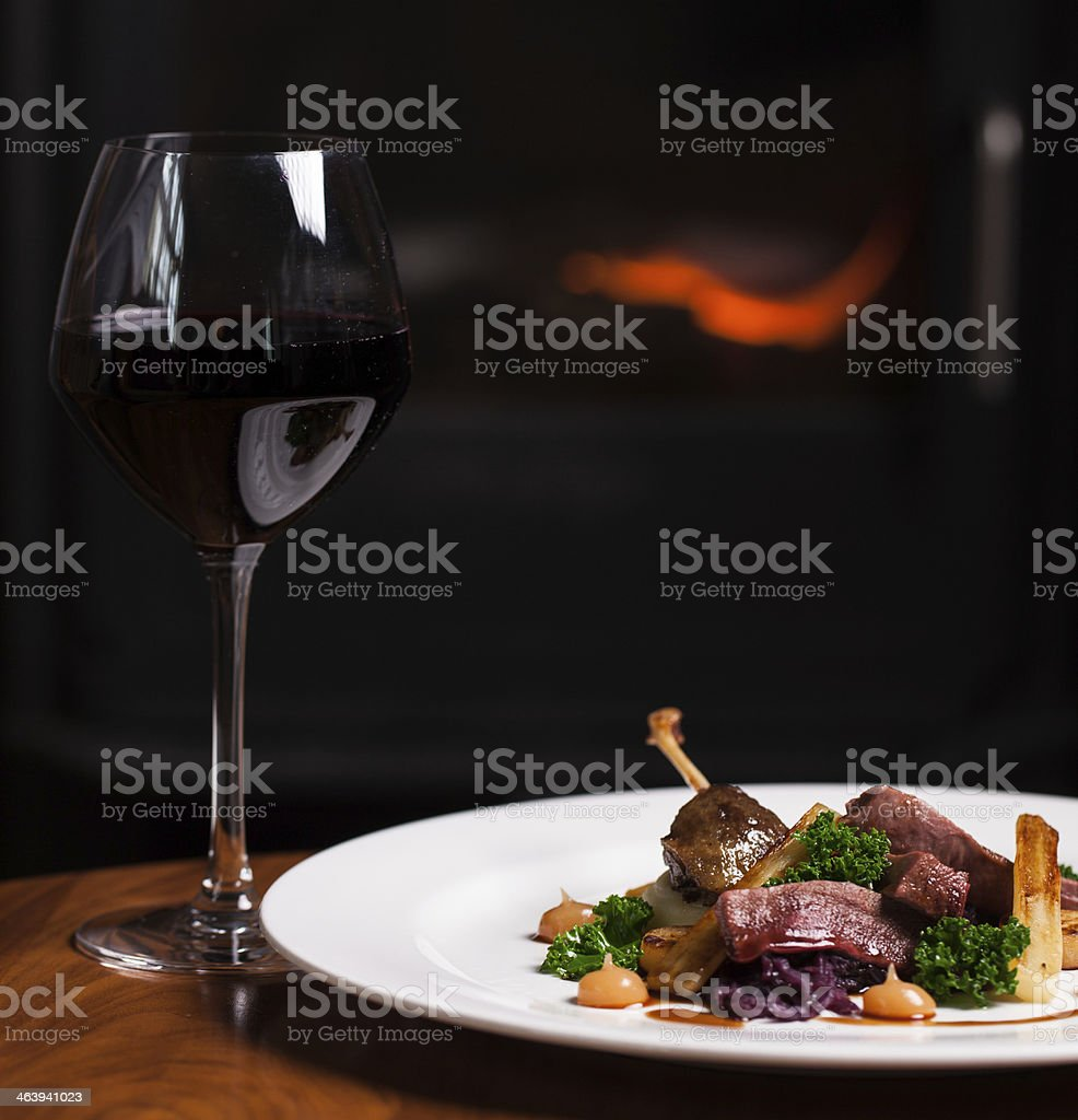 Roast Duck with Parsnips and a Glass of Red Wine stock photo