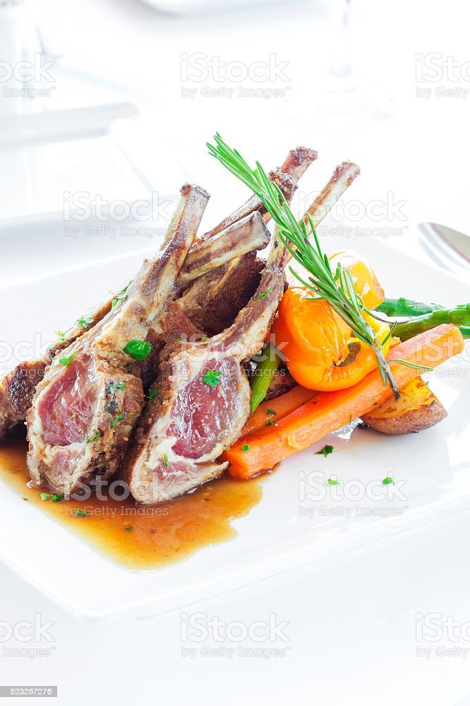 Roast lamb shanks served with vegetables and rosemary. stock photo