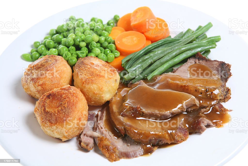 Roast lamb with gravy with vegetables and rolls on a plate royalty-free stock photo