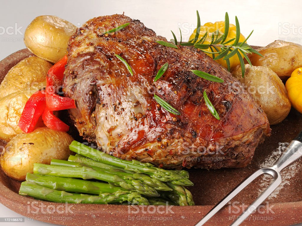 Roast leg of lamb on a platter with asparagus and potatoes stock photo