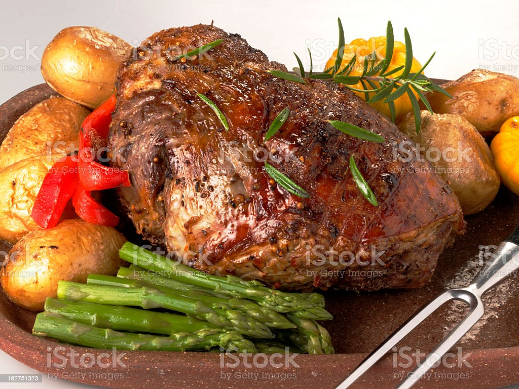 Roast leg of lamb surrounded by veggies on wooden tray stock photo