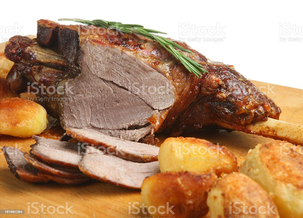 Roast leg of lamb with potatoes on carving board stock photo