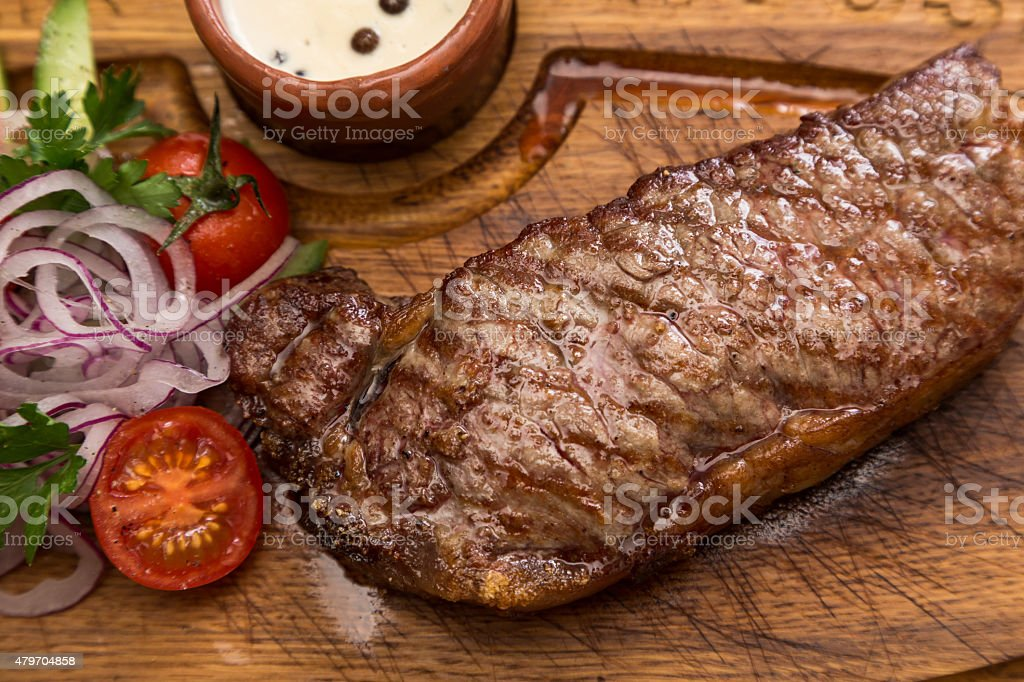roast meat steak with vegetable garnish and sauce stock photo