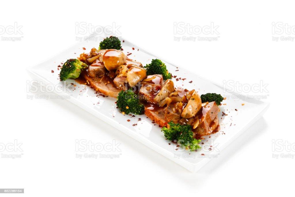 Roast pork and vegetables on white background