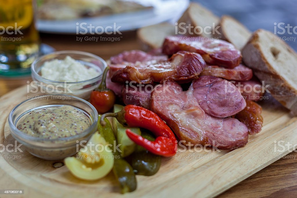 Roast pork knuckle with mustard and mixed pickles stock photo