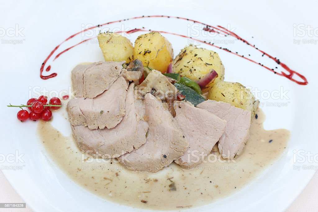 Roast pork with potatoes, vegetables and sauce stock photo