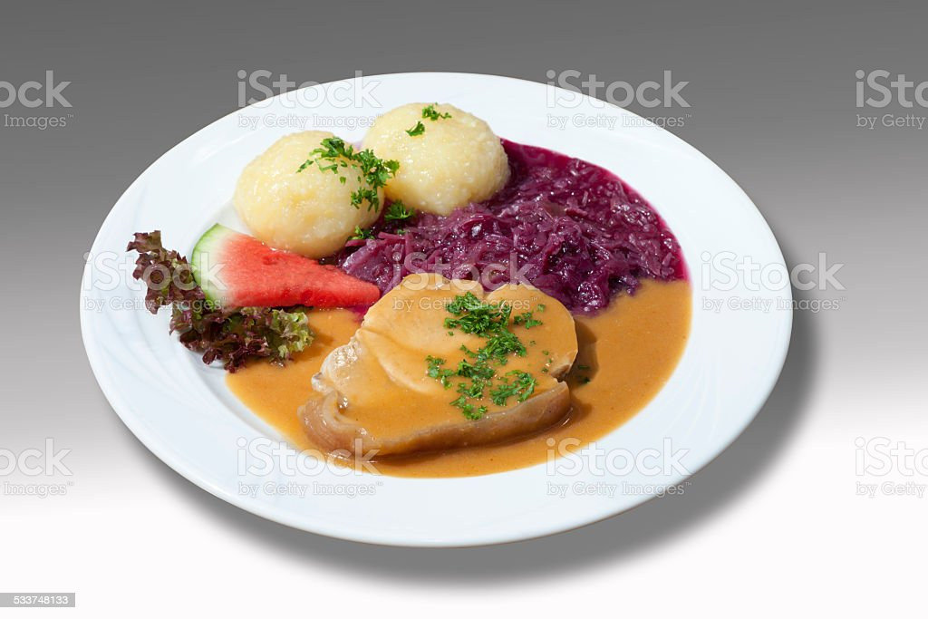 Roast pork with red cabbage and potato dumpling and sauce stock photo