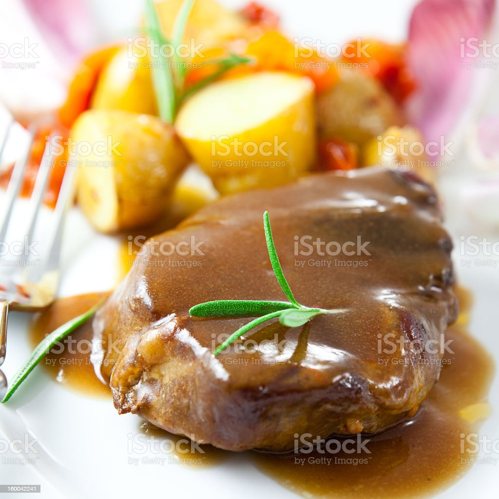 Roast pork with sauce and rosemary stock photo