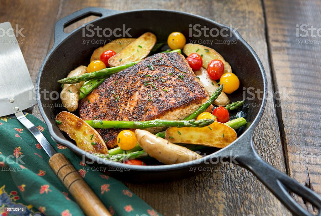 Roast salmon fillet with vegetables in a cast iron pan stock photo