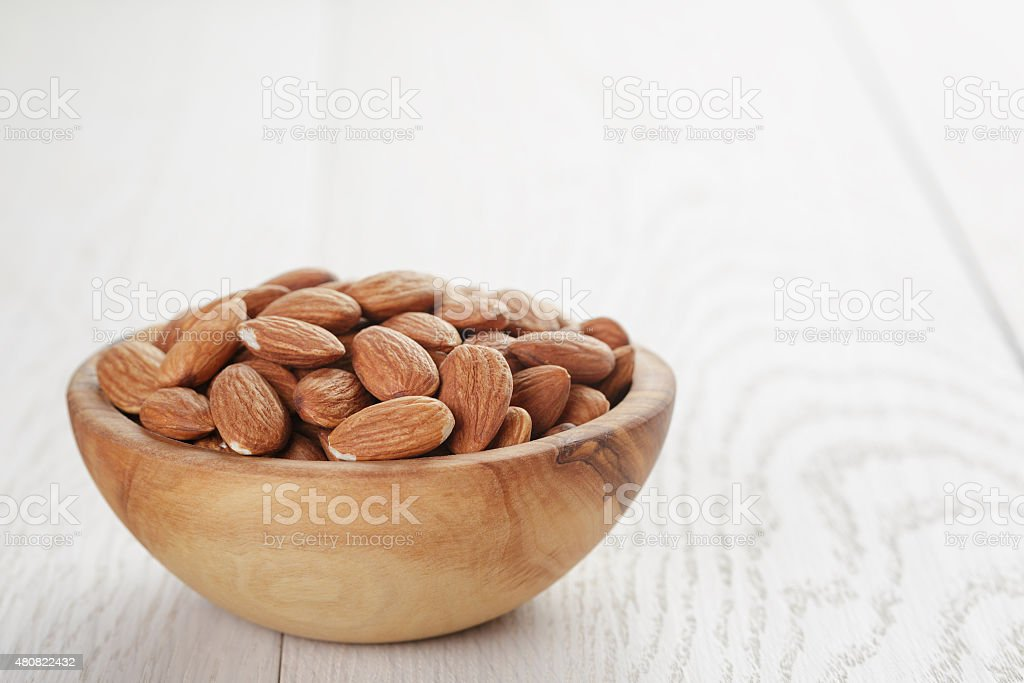 roasted almonds in bowl on white wooden table stock photo
