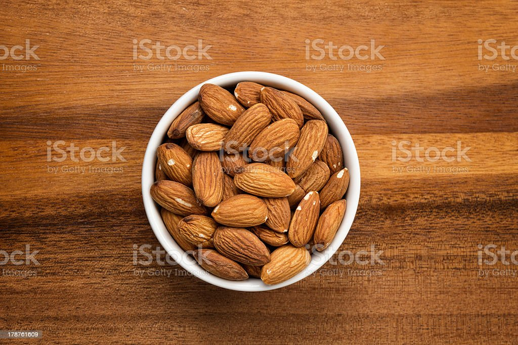 roasted almonds in white porcelain bowl stock photo