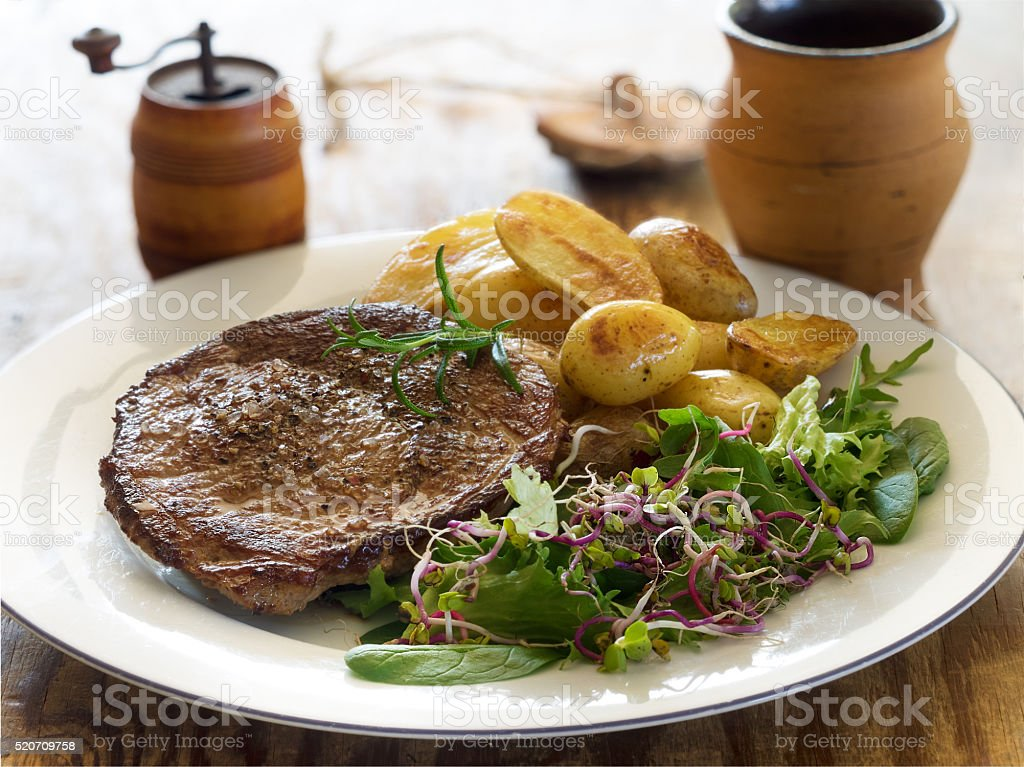 Roasted beef steak with baked potatoes and green salad royalty-free stock photo