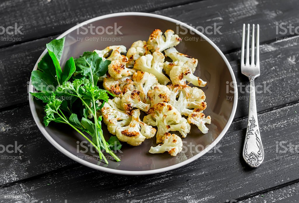 roasted cauliflower and fresh green salad on a brown plate stock photo