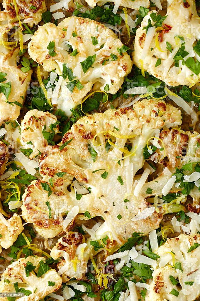 Roasted cauliflower slices of parmesan cheese, parsley and lemon zest stock photo