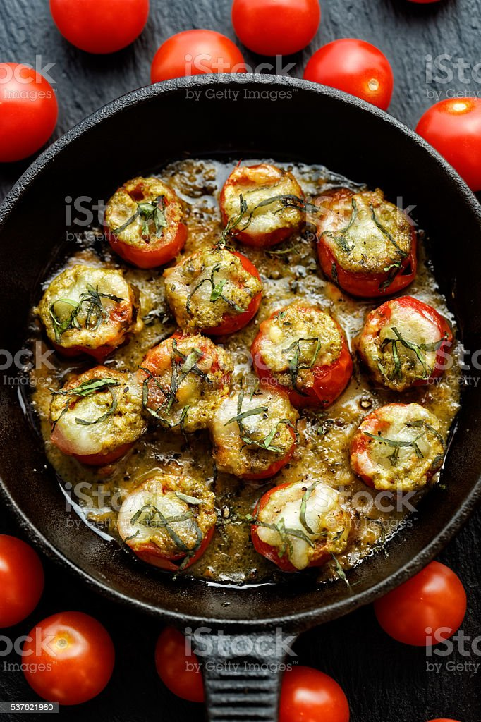 Roasted cherry tomatoes stuffed with herb pesto and mozzarella cheese stock photo