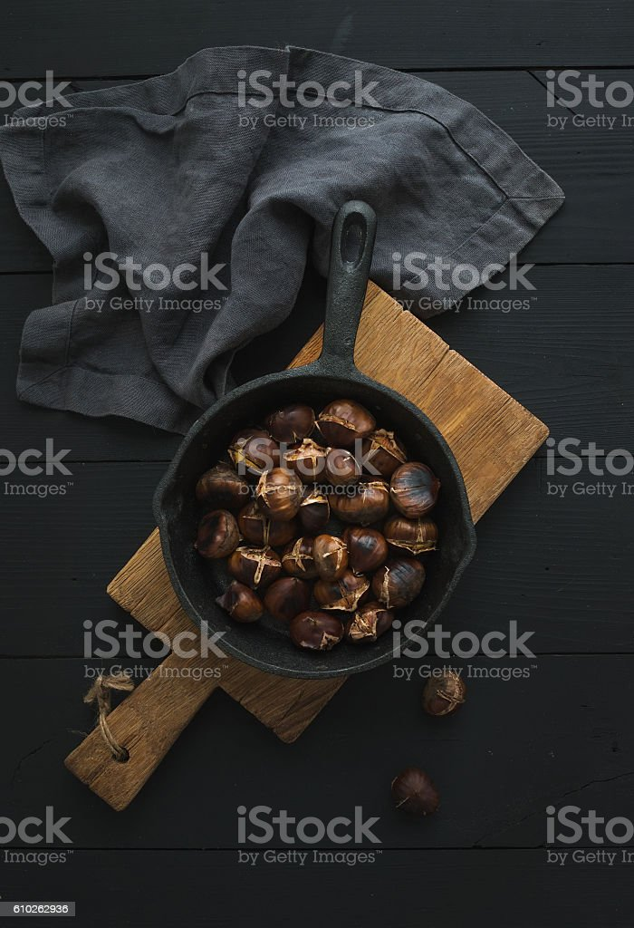 Roasted chestnuts in iron skillet pan stock photo