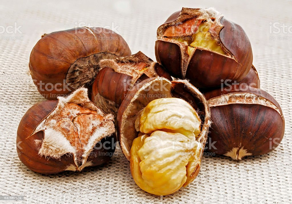 roasted chestnuts on a beige plate stock photo