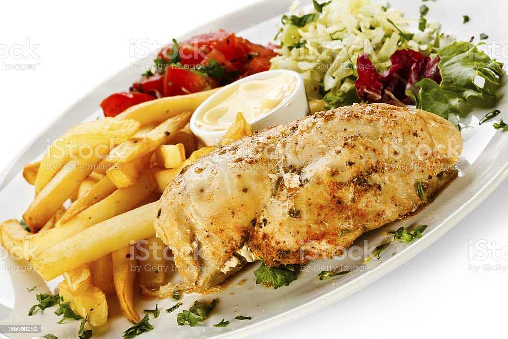 Roasted chicken breast, French fries and vegetables royalty-free stock photo