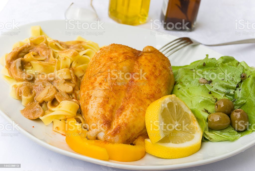 Roasted Chicken Breast with Tagliatelle and Lettuce royalty-free stock photo