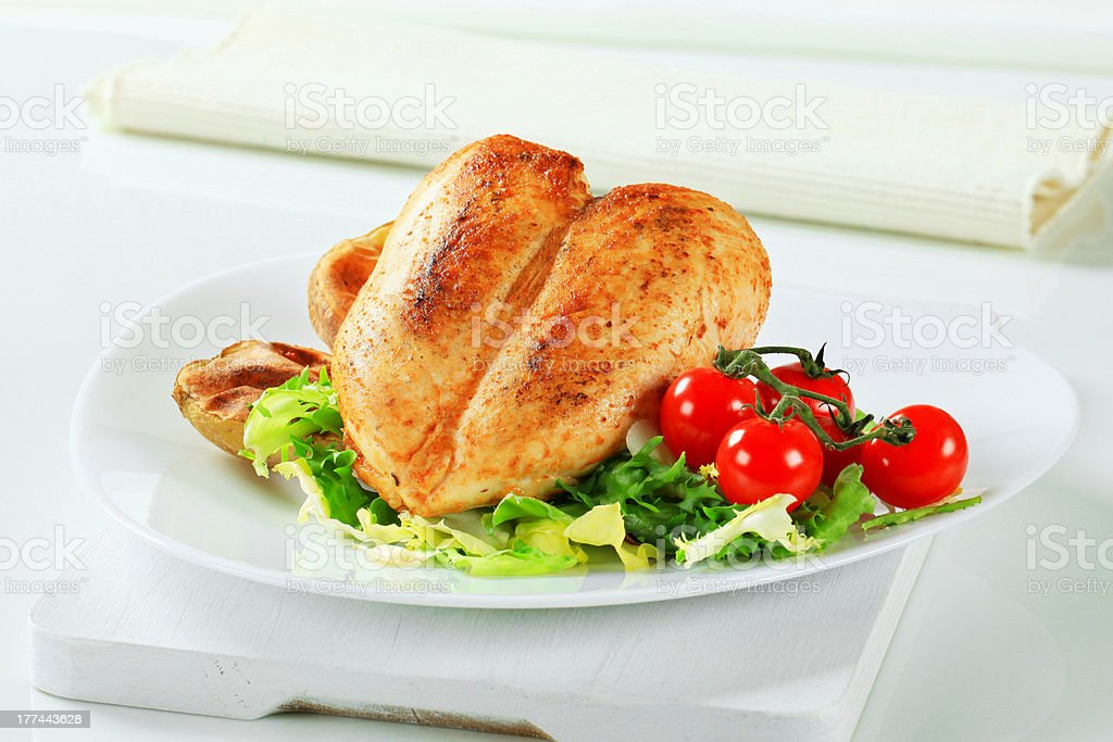 Roasted chicken breasts with potatoes and salad stock photo