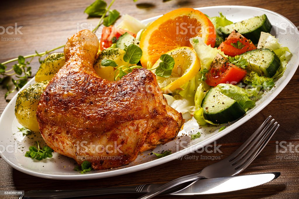 Roasted chicken leg, boiled potatoes and vegetables stock photo