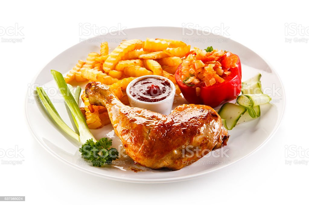Roasted chicken leg, French fries and vegetables stock photo