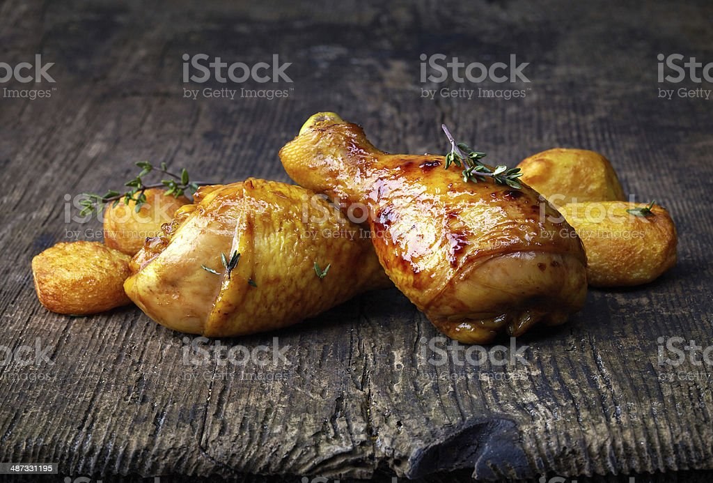Roasted chicken legs and potatoes on wooden cutting board stock photo