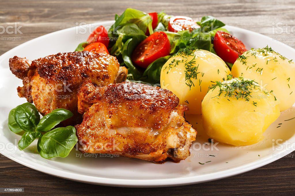 Roasted chicken legs, boiled potatoes and vegetables stock photo