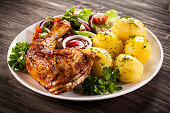 Roasted chicken legs, boiled potatoes and vegetables