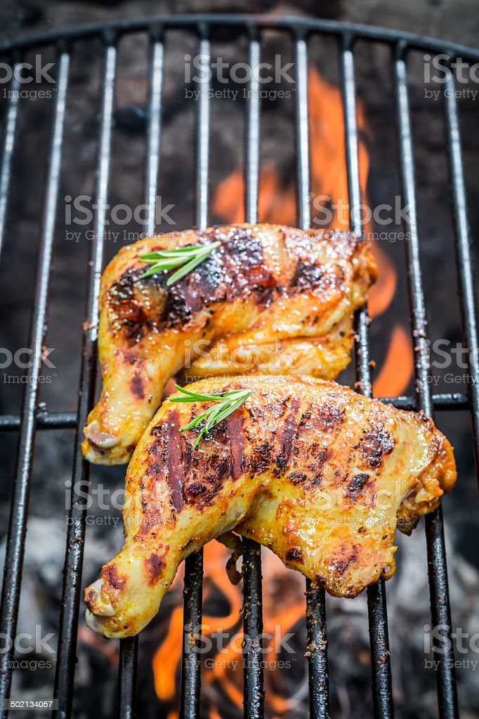 Roasted chicken legs on the old grill stock photo