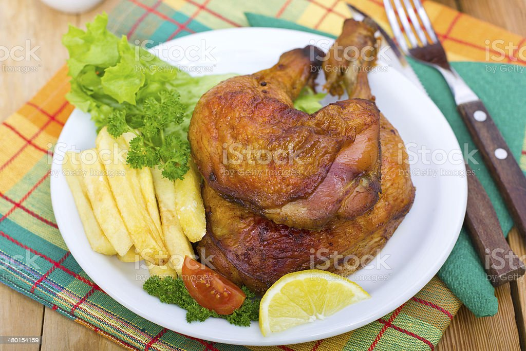 Roasted chicken legs on the plate stock photo