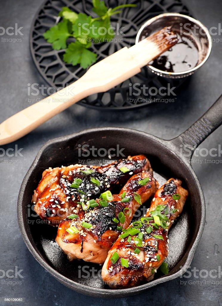 Roasted chicken legs teriyaki sauce in a frying pan stock photo