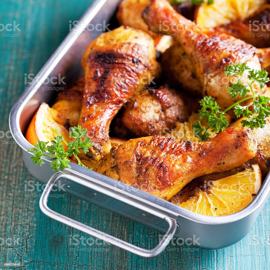Roasted chicken legs with oranges stock photo