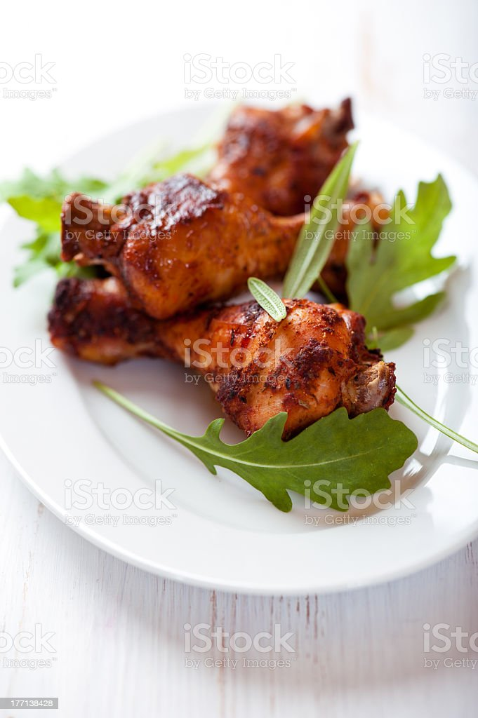 Roasted chicken legs with rocket leaves royalty-free stock photo