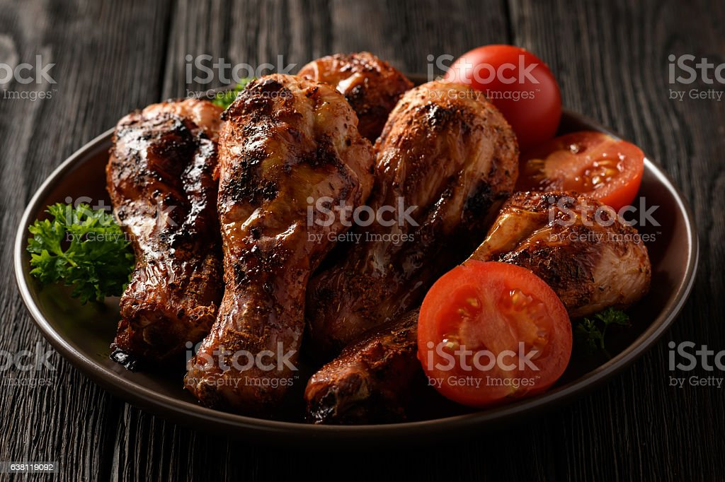 Roasted chicken legs with tomatoes on wooden background. stock photo