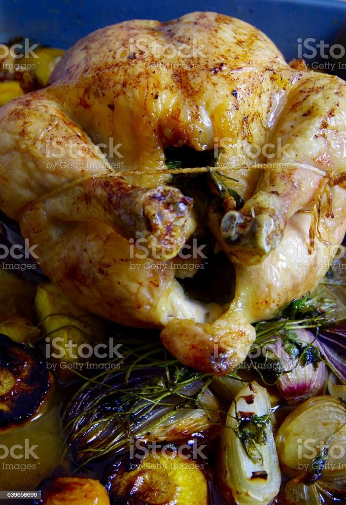 Roasted chicken on a bed of roast vegetables and herbs stock photo
