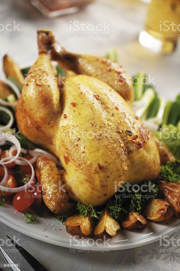 Roasted chicken on a bed of tomatoes and potatoes royalty-free stock photo